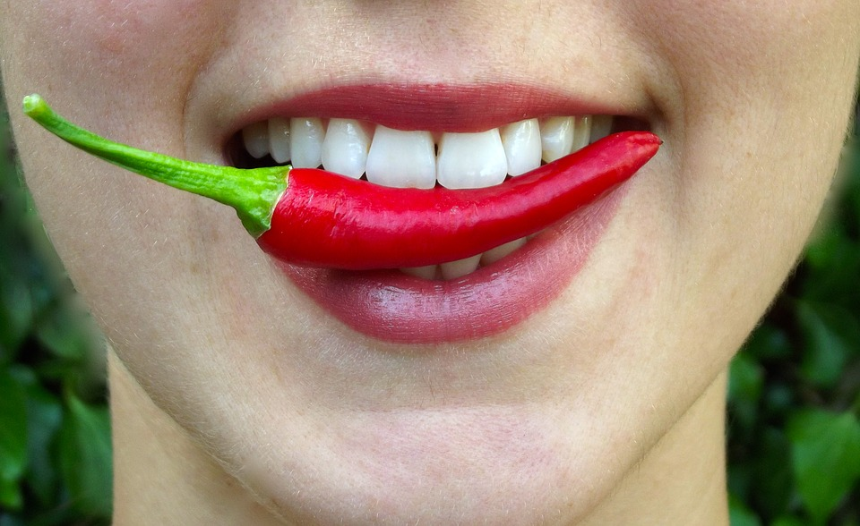 woman biting a red hot chili pepper