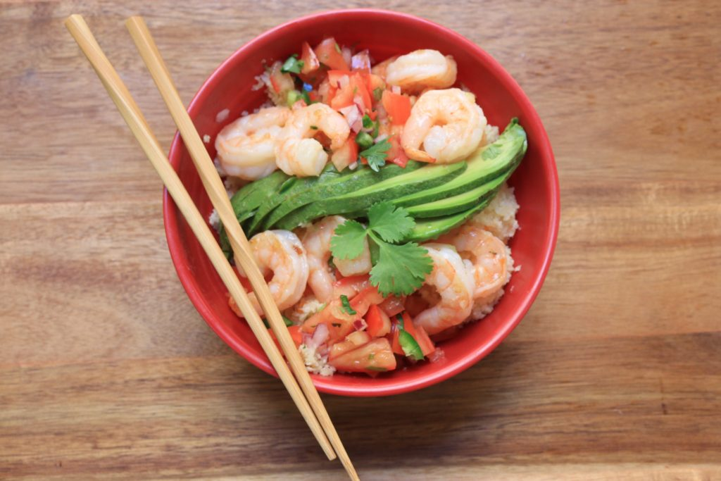 Our Mexican Rice bowl recipe is made with fresh cilantro, red onion, tomatoes and lime juice top a bed of cauliflower rice and and sauteed shrimp.